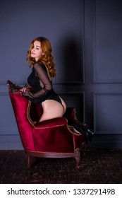 Sexy redhead woman with full hips and lace underwear in loft bedroom. Sexy and erotic concept. Vintage dark interior