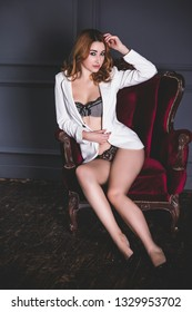 Sexy redhead woman in white jacket and lingerie at vintage interior. Lady with fashionable figure, full hips, nice legs