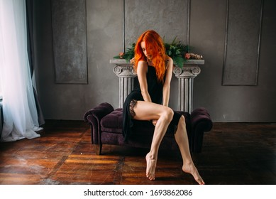 Sexy redheaded young woman  in a black dress with a high slit to the hip