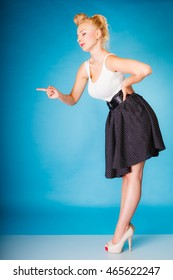 Sexy retro girl full length. Pin up woman with blonde hairdo and shaking wagging her finger gesture sign on blue background in studio.