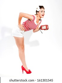 Sexy retro pin-up girl with radio and red lipstick wearing red striped shirt and white hot pants. Standing against white wall.