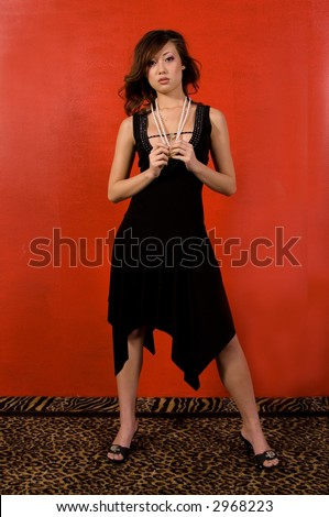 58768a7140f Sexy but sad Asian woman in a black dress and pearls standing in front of a