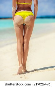 Sexy sandy woman buttocks on tropical beach background near ocean. close up outdoor shot of young woman in white bikini, sunbathing at sea shore. Yellow bikini
