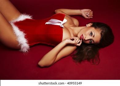 Sexy santa helper lie on red background