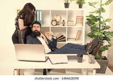 Sexy secretary personal assistant. Typical office life. Man bearded hipster boss sit in leather armchair office interior. Boss and secretary girl at workplace. Business people and office staff.