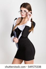 sexy secretary, portrait of beautiful brunette business lady with glasses and wearing in pinstripe suit
