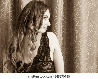 Sexy seductive woman by curtain. Sensual girl with long hair in lingerie. Female fashion. Back rear view.