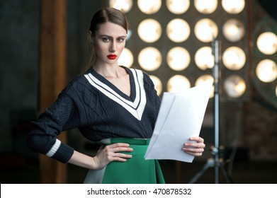 sexy serious  actress wearing sweater holding her scripts. Flash lights behind.