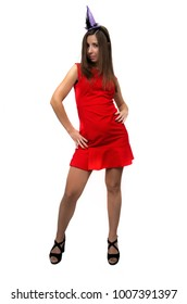 Sexy serious girl in red dress in stockings and in high heels shoes is standing with her legs wide apart isolated on white background. Woman with festive hat above her head.
