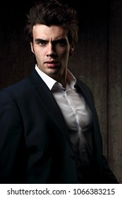 Sexy serious male business model posing in blue suit and white style shirt on dark shadow background. Fashion style contrast vogue portrait