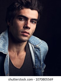 Sexy serious male model posing in blue jacket on dark shadow background. Fashion toned vogue portrait