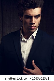 Sexy serious thinking business man posing in blue fashion suit and white style shirt on dark shadow background. Closeup toned fashion portrait