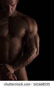 Sexy shirtless bodybuilder isolated on black background. Extreme strength, muscles and fitness.