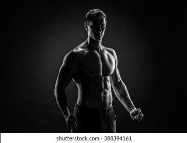 Sexy shirtless bodybuilder posing, looking at camera on black ba