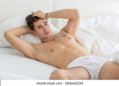 Sexy shirtless male model lying in bed wearing underwear and staring at the camera.