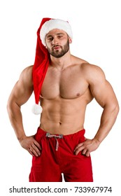 Sexy shirtless man in Santa hat isolated on a white background. Christmas costumes concept.