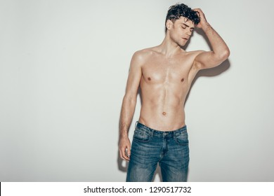 sexy shirtless young man in jeans posing on grey