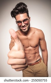 Sexy shirtless young man showing the thumbs up gesture while smiling.