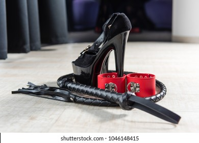 Sexy shoes and other toys for love bdsm games. High heel, leather whip and red handcuffs