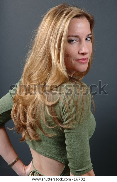 Sexy shot of a pretty model  with golden hair in green shiny top showing small of the back
