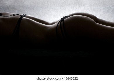 Sexy Silhouette of female spine and hips on a dark background