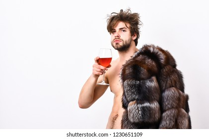 Sexy sleepy rich macho tousled hair drink wine isolated on white. Health and wellbeing. Richness and luxury concept. Rich athlete enjoy his life. Guy attractive rich posing fur coat on naked body.