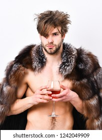 Sexy sleepy rich macho tousled hair drink wine isolated on white. Health and wellbeing. Richness and luxury concept. Guy attractive rich posing fur coat on naked body. Rich athlete enjoy his life.
