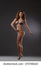 Sexy slender athlete in bikini on dark background