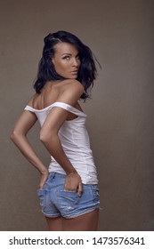 Sexy slender middle-aged woman in skimpy denim shorts and off the shoulder top turning to look at the camera with a sultry serious expression against a grey wall
