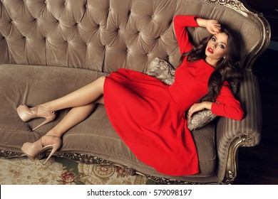 Sexy slim beautiful woman in red A-line dress lying on sofa in luxury interior and looking in camera. Fashion portrait from top point of view