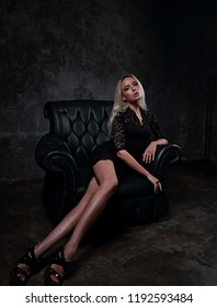 Sexy slim blod model with long legs in high heels sitting in fashion armchair in black dress and posing on dark dramatic background