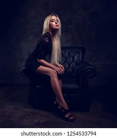 Sexy slim blod model with long legs in high heels sitting in fashion armchair in black dress and posing on dark dramatic background. Toned portrait