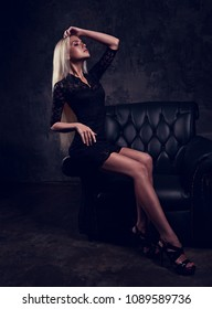 Sexy slim blod model sitting in fashion armchair in black dress and posing on dark dramatic background. Toned fashion portrait