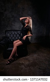 Sexy slim blod model sitting in fashion armchair in black dress and posing on dark dramatic background. Full lenght