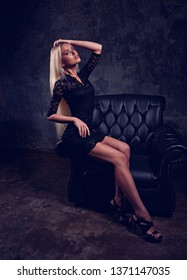 Sexy slim blod model sitting in fashion armchair in black dress and posing on dark dramatic background. Full lenght. Toned art portrait