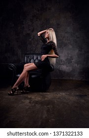 Sexy slim blod model sitting in fashion armchair in black dress and posing on dark dramatic background. portrait. Profile view