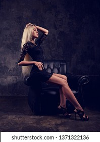 Sexy slim blod model sitting in fashion armchair in black dress and posing on dark dramatic background. portrait. Profile view. TOned