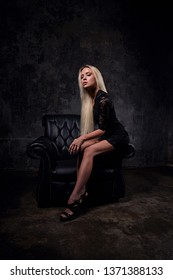 Sexy slim blod model sitting in fashion armchair in black dress and posing on dark dramatic background. Art