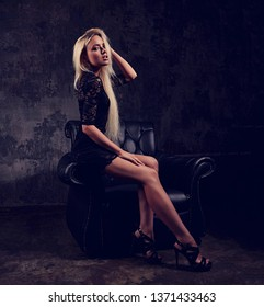 Sexy slim blod model sitting in fashion armchair in black dress and posing on dark dramatic background. Art toned portrait