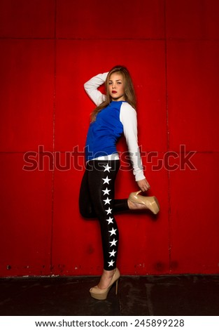 01aed32f76a0 Sexy slim blonde girl in legging and high heels posing against red wall