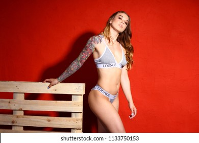 Sexy slim brunette girl with tattoo on a hand. Girl on a red background poses with wooden palette in sexy lingerie .