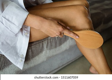 sexy slim woman's hips and legs wearing white classic underclothes, she using brush for massaging body at home. Cellulite treatment, dry brushing