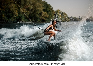 Sexy smiling brunette woman wakesurfing on a board down the blue water on sunny day