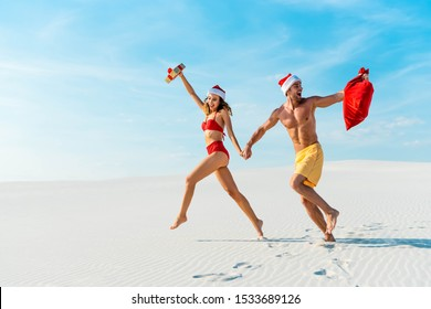 sexy and smiling girlfriend holding gift and boyfriend with santa sack running on beach in Maldives
