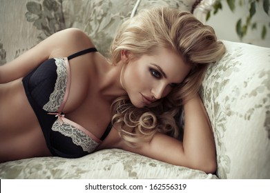 Sexy smiling woman relaxing in bed covering her breast.