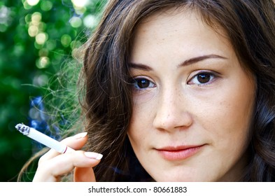 Sexy smoking woman with beautiful face posing outdoors