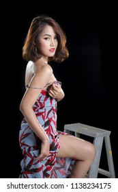 Sexy South East Asian woman posing in leaf print slinky split front periwinkle blue dress in a photography studio, sitting on stair on the black background.