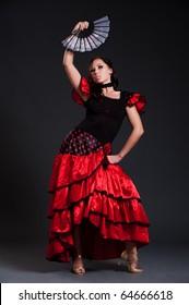 sexy spanish woman dancing over dark background