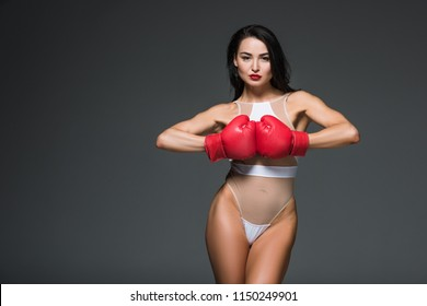 sexy sportive woman in white swimwear and boxing gloves looking at camera isolated on grey
