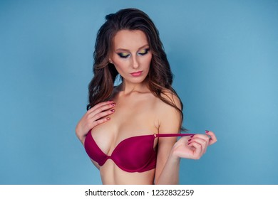 Sexy sports woman in red swimsuit pose in studio blue background.sensual brunette hairstyle and makeup girl leggy model wearing lingerie